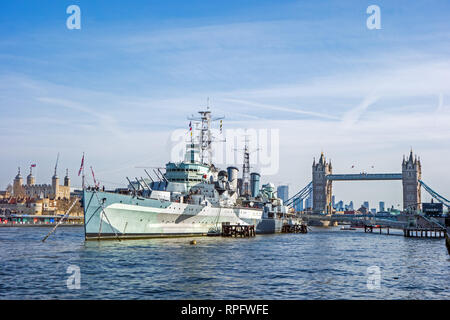 HMS Belfast moored on the River Thames in front of Tower Bridge and the Tower of London - Stock Image