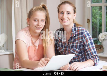 Female Home Tutor Helping Girl With Studies Using Digital Tablet At Camera - Stock Image