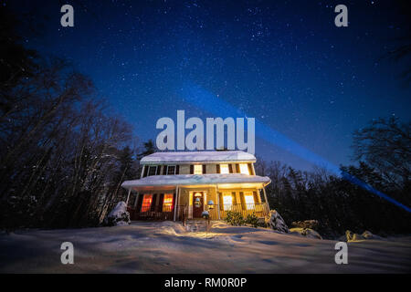 A starlit sky shines down on a wintery New England home shrouded in snow. - Stock Image