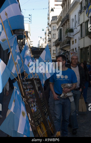 Local men walking past a stall selling Argentinian flags - Stock Image