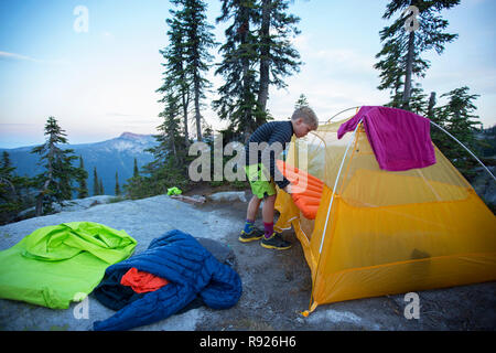 Photograph of a 10 year old boy near a tent preparing for camping, Selkirk Mountains, Sandpoint, Idaho, USA - Stock Image