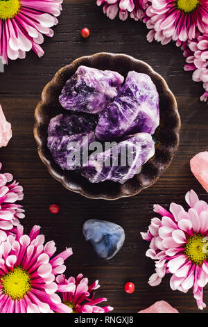 Amethyst with Rose Quartz and Blue Lace Agate with Pink Mums on Dark Wood - Stock Image