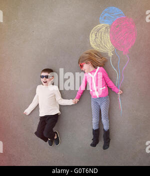 Children are holding hands outside with colorful chalk balloons sketched out on cement for a creative, craft or - Stock Image