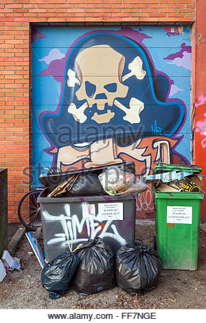 Trash in front of a graffiti (pirate with a skull on his hat) - street art in Grenoble (France) - Stock Image