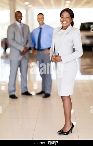 portrait of African car saleswoman with team on background - Stock Image