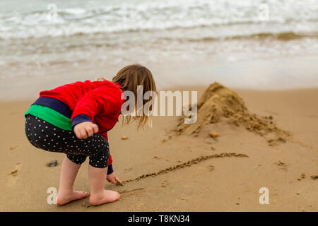 Candid colour photograph taken from behind young girl drawing in sand on beach waterfront. Poole, Dorset, England. - Stock Image