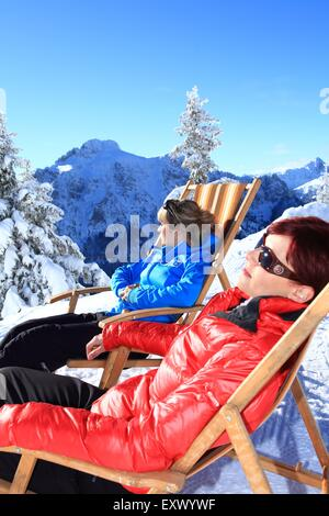 Two women in lounger in snow, Tegelberg, Ammergau Alps, Allgaeu, Bavaria, Germany, Europe - Stock Image