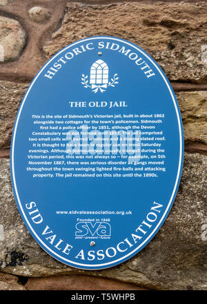 Blue plaque sign telling about the old barred windows of Sidmouth Jail left in a wall as part of a new housing development. Town jail bars. - Stock Image
