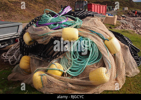 A pile of sea fishing gear, ready for use by the local fishing industry, on a harbour, including bouys, ropes and netting also with vehicle trailers - Stock Image