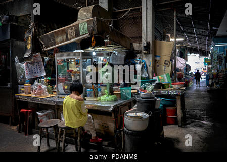 Child alone at a dimly lit Thailand market back street stall. - Stock Image