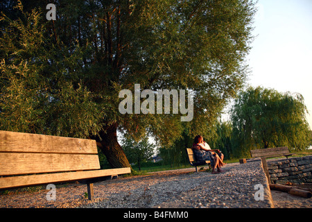 Couple enjoying a late afternoon sunset on a park bench, Dobbs Ferry, NY, USA - Stock Image