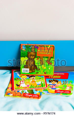 Poznan, Poland - November 18, 2018: Colorful Polish child book about a bear on a bed. - Stock Image