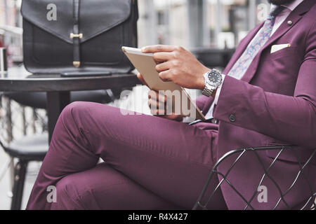 A beautiful African American businessman reads a menu in a cafe - Stock Image