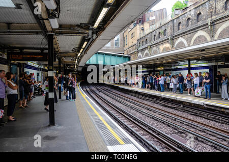 People wait on the platforms at Sloane Square London Underground Station for a train to arrive. - Stock Image