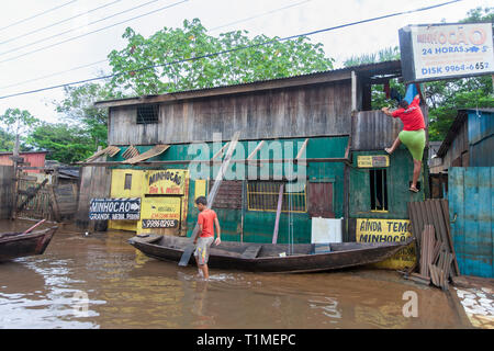 2015 flooding in Brazilian Amazon, woman climbs her house at Taquari district, Rio Branco city, Acre State. Floods have been affecting thousands of people in the state of Acre, northern Brazil, since 23 February 2015, when some of the state's rivers, in particular the Acre river, overflowed. Further heavy rainfall has forced river levels higher still, and on 03 March 2015 Brazil's federal government declared a state of emergency in Acre State, where current flood situation has been described as the worst in 132 years. One of the worst affected areas is the state capital, Rio Branco, where leve - Stock Image