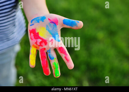 a child's hand is soiled in multicolored finger paints close-up on a grass background. - Stock Image