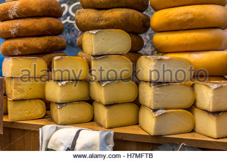Handmade cheeses exposed at the artisan market stop. - Stock Image