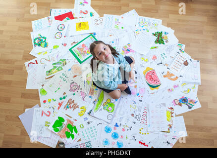 Happy five years student over her whole year homework. Overhead shot - Stock Image