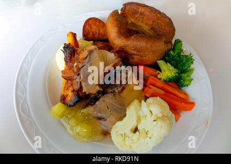 Traditional English Sunday lunch Roast Pork with Yorkshire Pudding, mashed and roast potatoes broccoli cauliflower carrots apple sauce and gravy - Stock Image