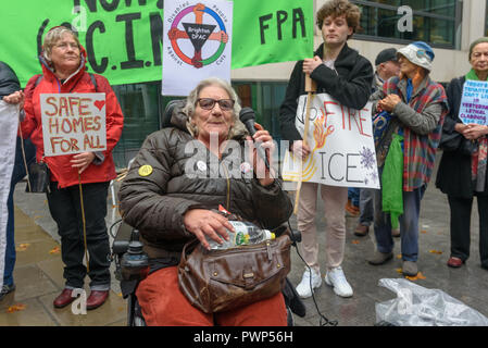 London, UK. 17th October 2018. A woman in a wheelchair speaks for Disable People Against Cuts, reminding us how much more vulnerable the disabled are in fires at the protest outside the Ministry of Housing, Communities and Local Government by residents living in tower blocks covered in Grenfell-style cladding, Fuel Poverty Action, and Grenfell campaigners demanding that the government make all tower-block homes safe and warm. Credit: Peter Marshall/Alamy Live News - Stock Image