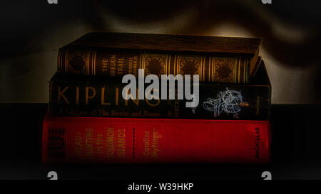 Vintage still life with stacked up books on dark background closed on a desk  literacy concept - Stock Image