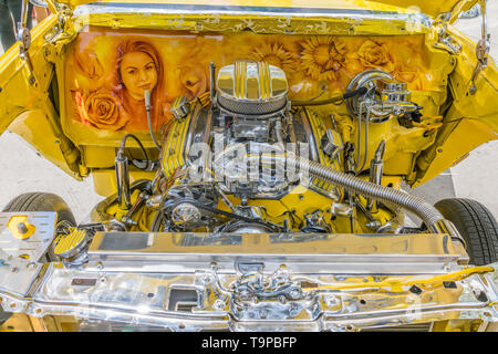 A view of the chromed and painted engine compartment, including hand painted woman's portrait and flowers, on a bright yellow Chevrolet lowrider car t - Stock Image