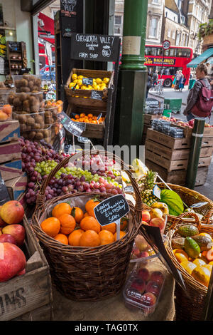 Chegworth Valley Farm Shop with farmers attractive rustic fruit display, red London bus in background, at Borough Market Southwark London UK - Stock Image