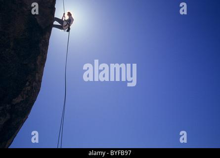 Female rock climber rappelling in Joshua Tree National Park, California, USA - Stock Image