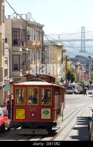 The number 25 travels up the hill out of Chinatown in San Francisco with a load of passengers and the Bay Bridge - Stock Image
