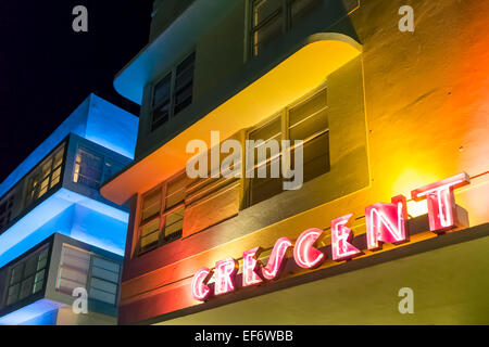 Crescent Hotel's Art Deco yellow facade illuminated at night by red neon sign along Deco Drive on Miami Beach, - Stock Image