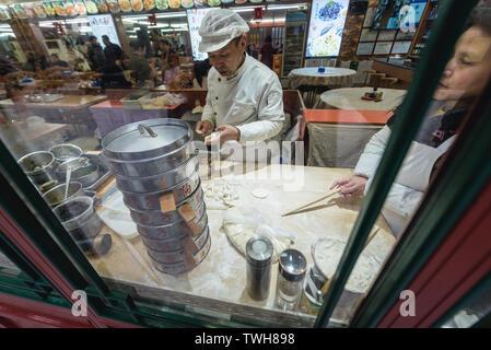 Indoor food stand with dumplings on Qianmen Street in Beijing, China - Stock Image