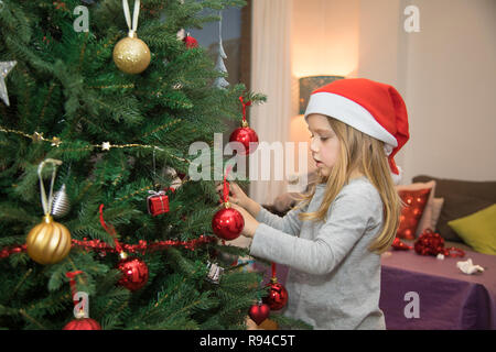 four years blonde cute child with red Santa Claus hat, decorating Christmas tree at home - Stock Image