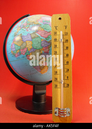 Climatic heating up Globe with a thermometer as symbol for the climatic heating up and the that heat the atmosphere - Stock Image