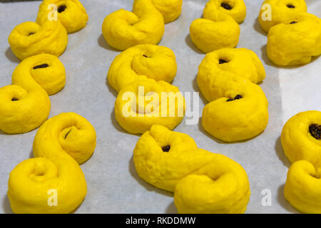 Yellow homemade saffron bread part of Swedish Christmas tradition ready for the oven. - Stock Image