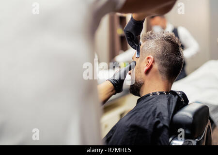 A hipster man client visiting haidresser and hairstylist in barber shop. - Stock Image
