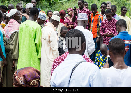 Ananguié, Côte d'Ivoire - June 10, 2017: men in boubou and hats on one side and another group of people on the side, all look down. To say a farewell  - Stock Image