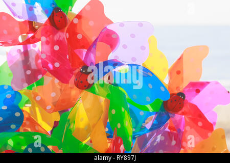 Colourful toy windmills on display at beachside in Southwold, a popular seaside town in the UK - Stock Image