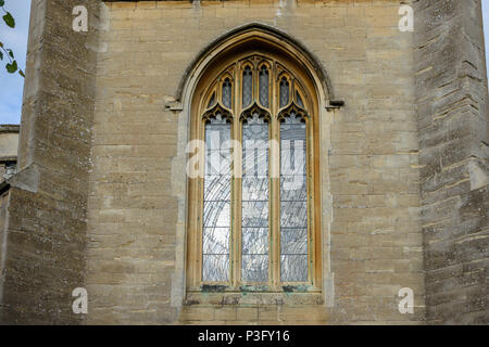 Outside view of a stained glass window of Christchurch Bradford on Avon lit by the evening sunlight - Stock Image