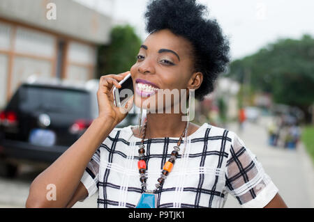 Portrait of pretty African woman in communication in the street with a beautiful smile - Stock Image