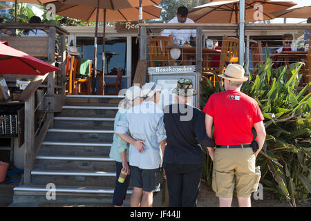 Beach visitors reading the menu outside the Beachcomber Restaurant at Crystal Cove State Park California USA - Stock Image