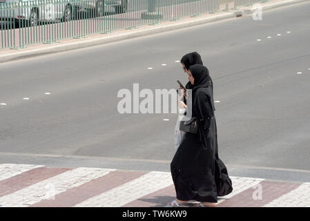 Muslim women watching cell phone and crossing the street, Abu Dhabi, United Arab Emirates - Stock Image