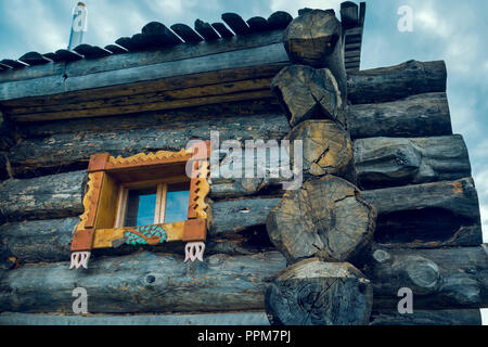 Close-up of a log hut with a window framed by carved platbands against the blue sky - Stock Image