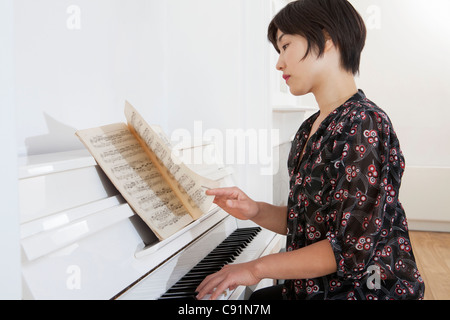 Woman playing piano at home - Stock Image