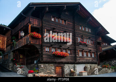 A large and richly-ornamented 17th-c. house on the village square of Ferden, Lötschental Valley, Valais, Switzerland - Stock Image