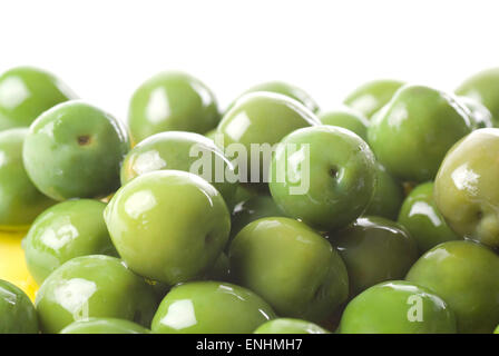 Green olives in olive oil close up. - Stock Image