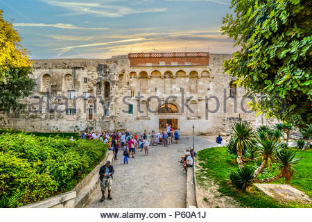 Tourists gather in tour groups outside the ancient Golden Gate to the Diocletian's Palace section of Old Town Split, Croatia in early autumn. - Stock Image
