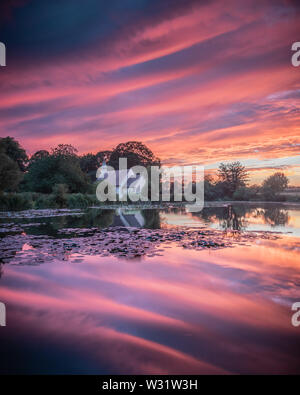A vibrant sunset reflecting on a lake with a church across the water - Stock Image
