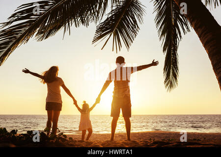 Happy family of mother father and daughter under palm - Stock Image