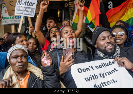 London, UK. 6th April 2019. After Class War had pushed aside the barriers the protest continued on the steps of the Dorchester Hotel in Mayfair against the multi-billionaire Sultan of Brunei who has announced death by stoning as a punishment for gay sex, adultery and blasphemy demonstrating against this barbaric abuse of international law and human rights and calling for a boycott of his hotels around the world. The doors were locked and the protesters made only token efforts to enter the hotel, blocking the entrance with a noisy protest on the steps. Peter Marshall/Alamy Live News - Stock Image