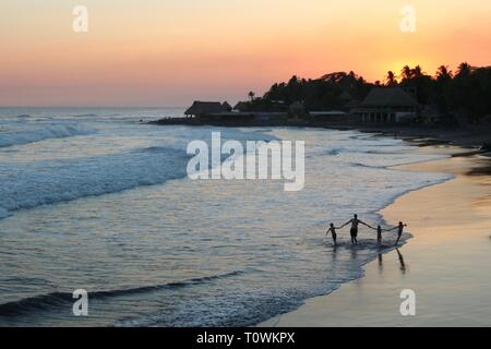 Silhouette of father and three children walking in the surf during sunset on a tropical beach in El Salvador - Stock Image